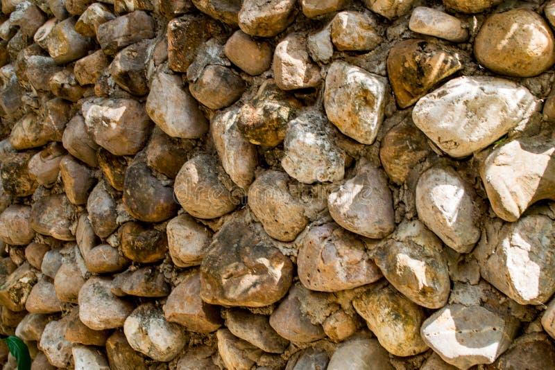 Las paredes de piedras marrones se enyesan contra la pared imagen de archivo