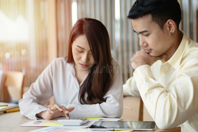 Las parejas asiáticas descontentas calculan ingresos y gastos para reducir gastos innecesarios. Conceptos de planificación y fin fotografía de archivo