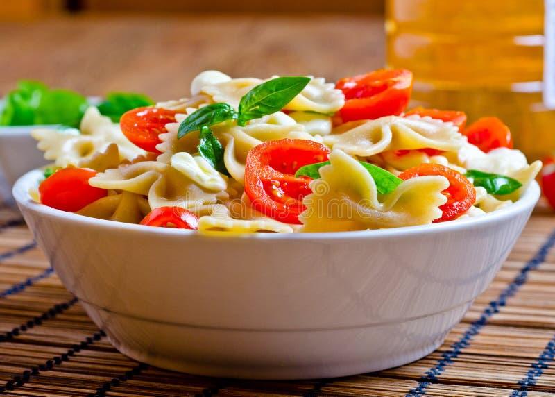 Las pastas con albahaca, los tomates y el queso italiano llamaron la mozzarella imagen de archivo
