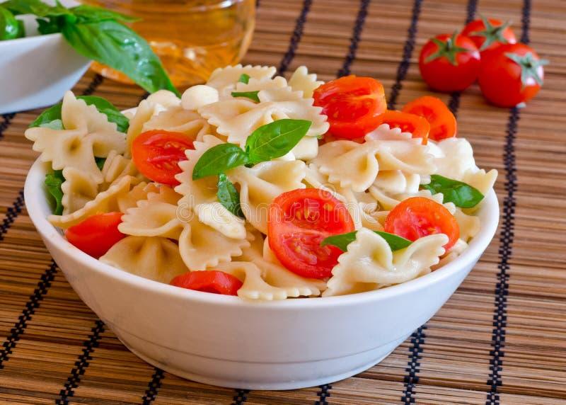 Las pastas con albahaca, los tomates y el queso italiano llamaron la mozzarella foto de archivo libre de regalías