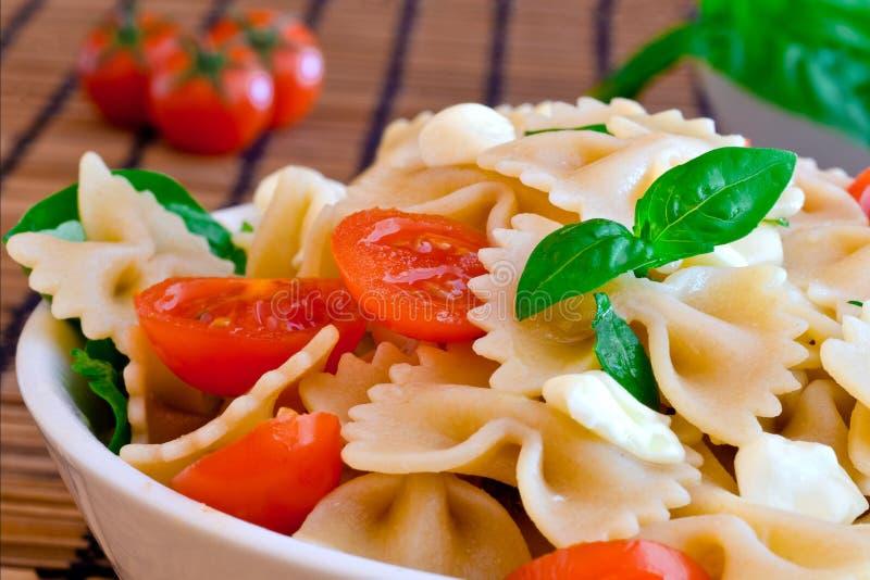 Las pastas con albahaca, los tomates y el queso italiano llamaron la mozzarella imágenes de archivo libres de regalías