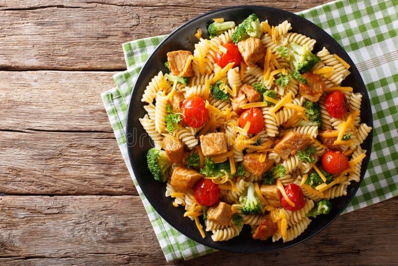 Las pastas de Fusilli con cerdo, el bróculi, los tomates y el queso chedarizan c fotografía de archivo