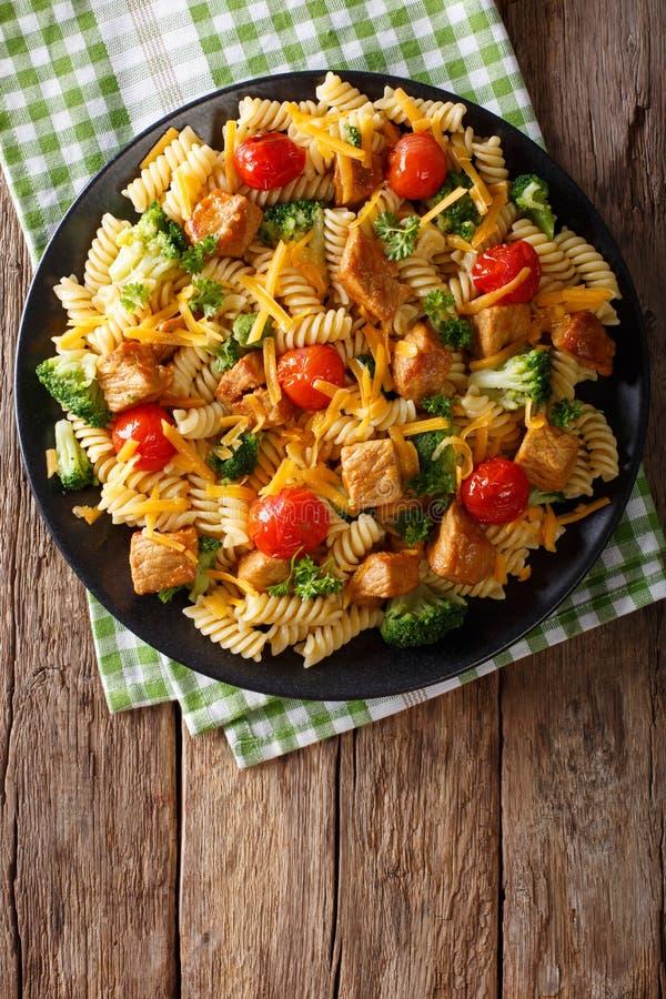 Las pastas de Fusilli con cerdo, el bróculi, los tomates y el queso chedarizan c imagenes de archivo