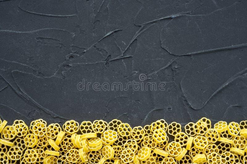 Las pastas descompuestas hermosas del ruote de los macarrones con una parte inferior en un negro texturizaron el fondo Opinión de imagen de archivo