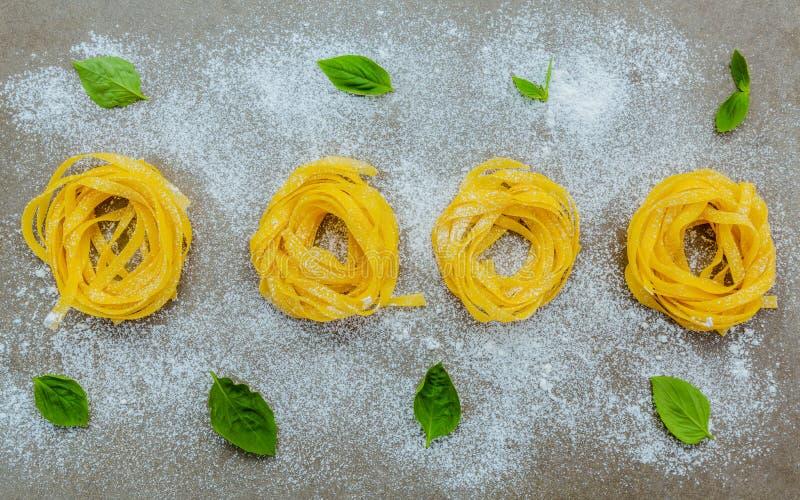 Las pastas italianas del concepto de la comida con albahaca dulce con la harina pusieron encendido fotografía de archivo