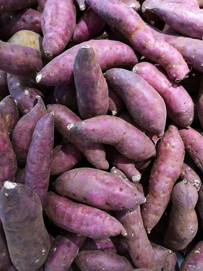 Las patatas dulces, crudas de la granja se incluyen en venta en supermercados fotografía de archivo