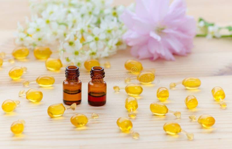 Las pequeñas botellas marrones con los aceites esenciales del neroli y de la rosa, cápsulas del oro del cosmético natural, florec imagenes de archivo