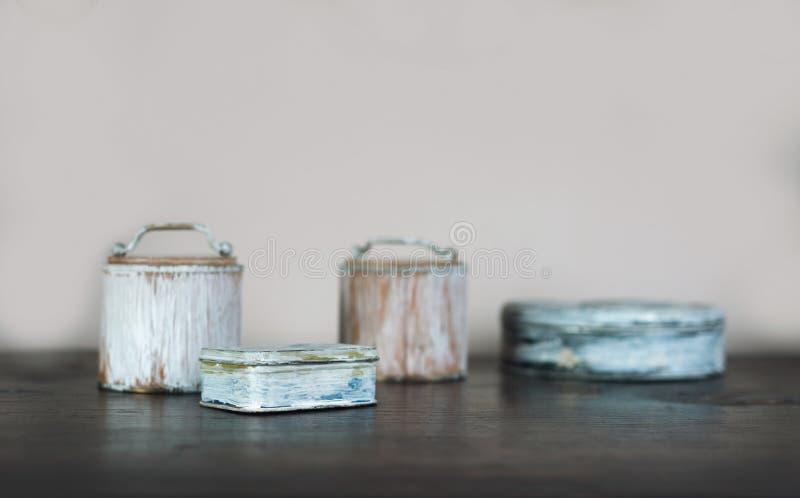 Las pequeñas cajas viejas pintaron blanco en la tabla de madera foto de archivo