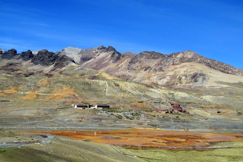 Las pequeñas casas del pueblo con los tejados rojos acercan a la montaña roja y al lago anaranjado fotos de archivo libres de regalías
