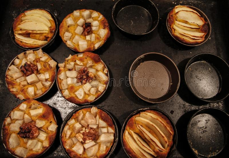 Las pequeñas empanadas de manzana hechas en casa cocieron recientemente cada uno en su molde fotos de archivo libres de regalías