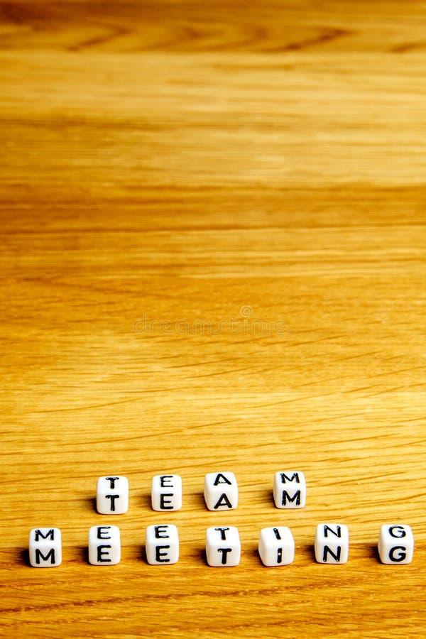 Las pequeñas estatuillas miniatura con poco cortan la formación en cuadritos de la reunión del equipo de la palabra como parte de imagen de archivo libre de regalías