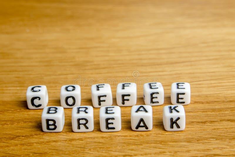 Las pequeñas estatuillas miniatura con poco cortan la formación en cuadritos del descanso para tomar café de la palabra como part imagen de archivo