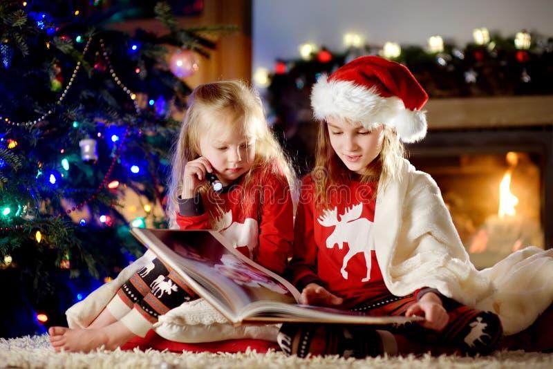 Las pequeñas hermanas felices que leen una historia reservan juntas por una chimenea en una sala de estar oscura acogedora el Noc imagenes de archivo