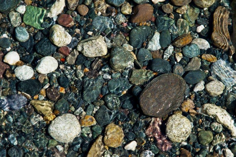 Las pequeñas piedras multicoloras en el banco de una montaña fluyen con agua glacial cristalina Visión superior foto de archivo libre de regalías