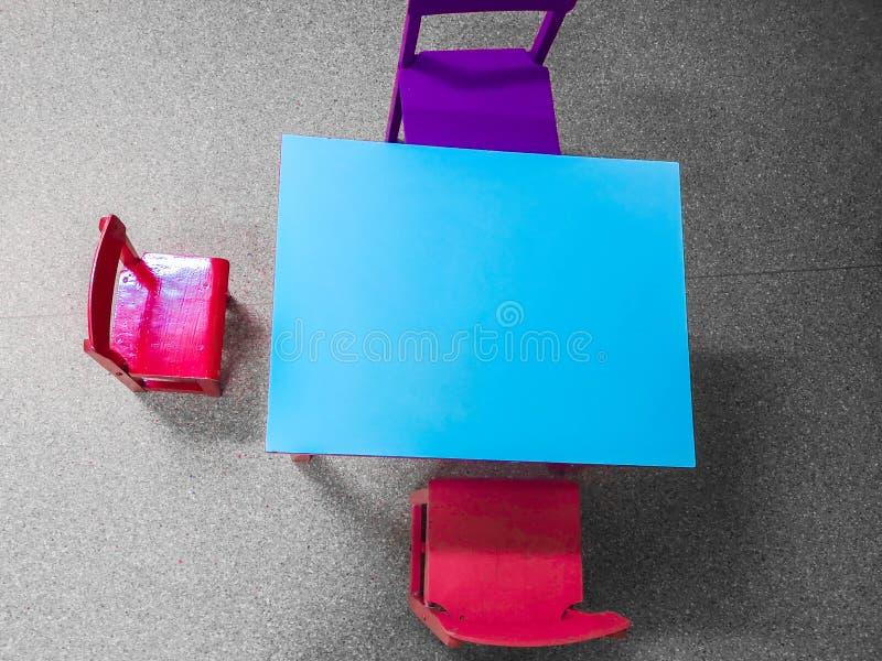 Las pequeñas tablas y sillas cerca de la pizarra en la pared en niños aporrean foto de archivo