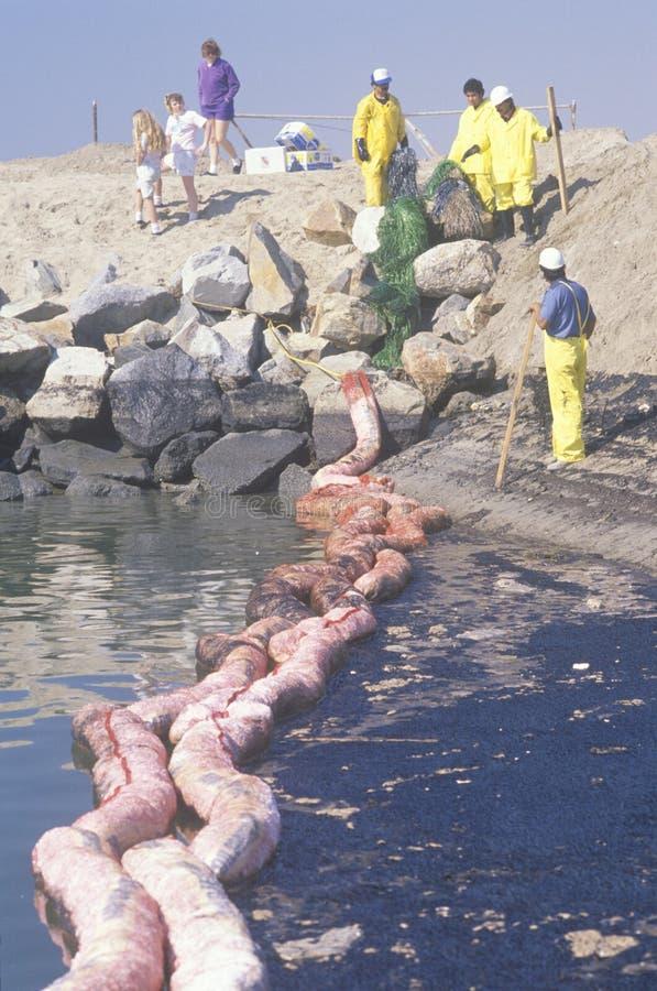Las personas de ecologistas limpian un derramamiento de petróleo imagen de archivo