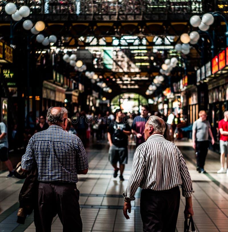 Las personas mayores de envejecimiento que tomaban un paseo en el pasillo del mercado central de Budapest apretaron con la gente fotografía de archivo libre de regalías