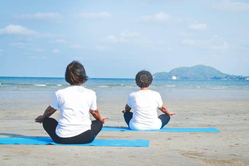 Las personas mayores ejercitan yoga en el mar fotografía de archivo