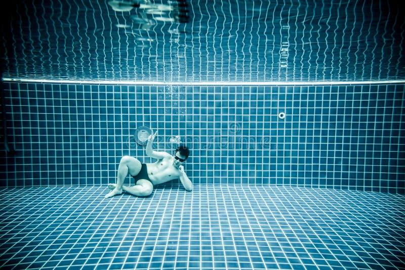 Las personas mienten debajo del agua en una piscina fotografía de archivo