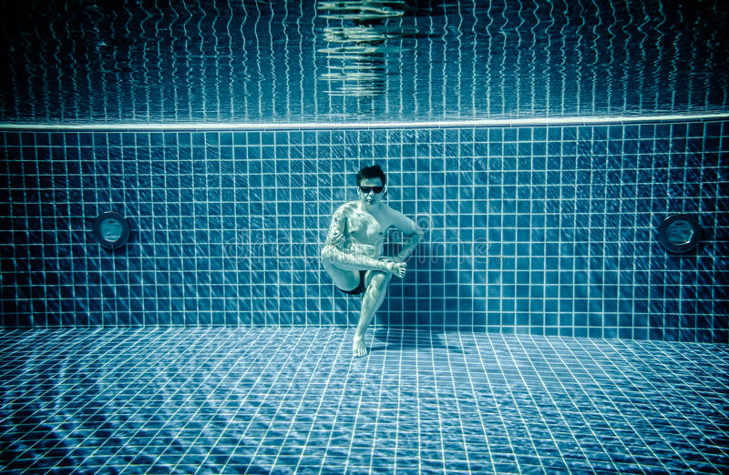Las personas mienten debajo del agua en una piscina fotos de archivo