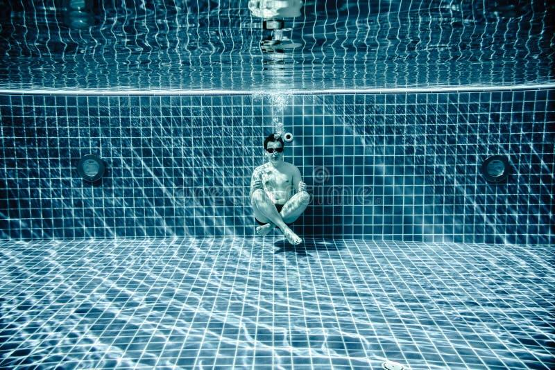 Las personas mienten debajo del agua en una piscina imagen de archivo libre de regalías