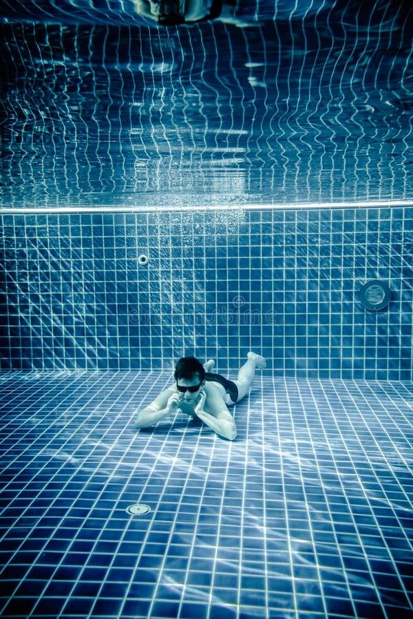 Las personas mienten debajo del agua en una piscina imágenes de archivo libres de regalías