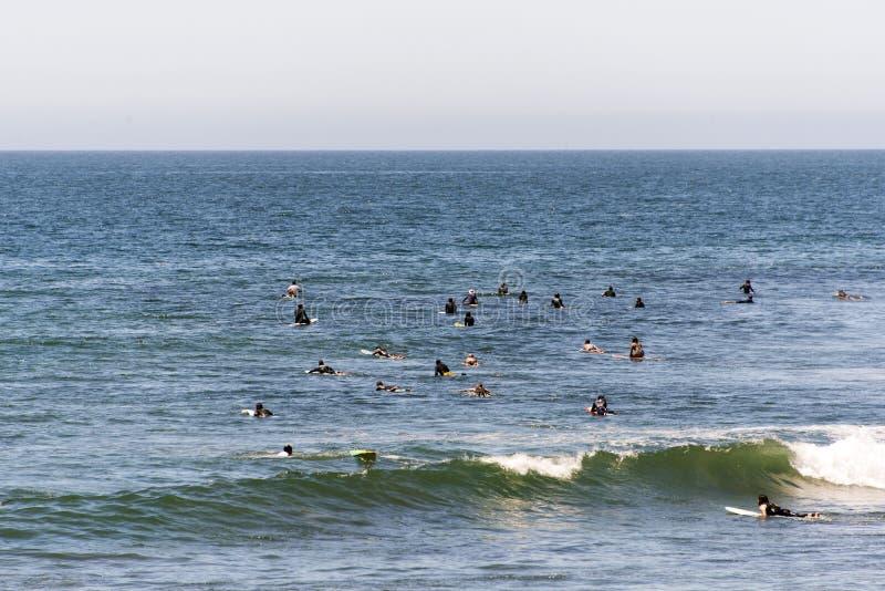 Las personas que practica surf que esperan la onda siguiente en el Malibu varan, California en tiempo de verano fotos de archivo