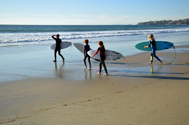 Las personas que practica surf jovenes van a la resaca en la playa en Laguna Beach, California de la calle del roble imagenes de archivo
