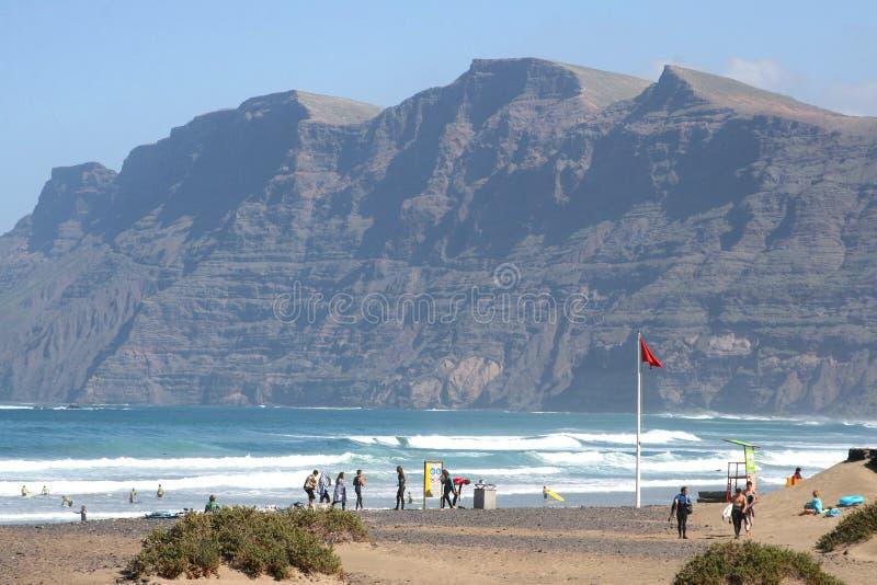 Las personas que practica surf varan en Famara, Lanzarote, España imagenes de archivo