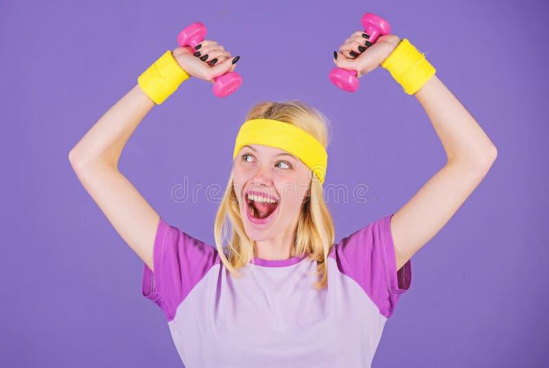 Las pesas de gimnasia del control de la muchacha llevan pulseras Concepto del deporte y de la aptitud Mujer que ejercita con pesa fotos de archivo