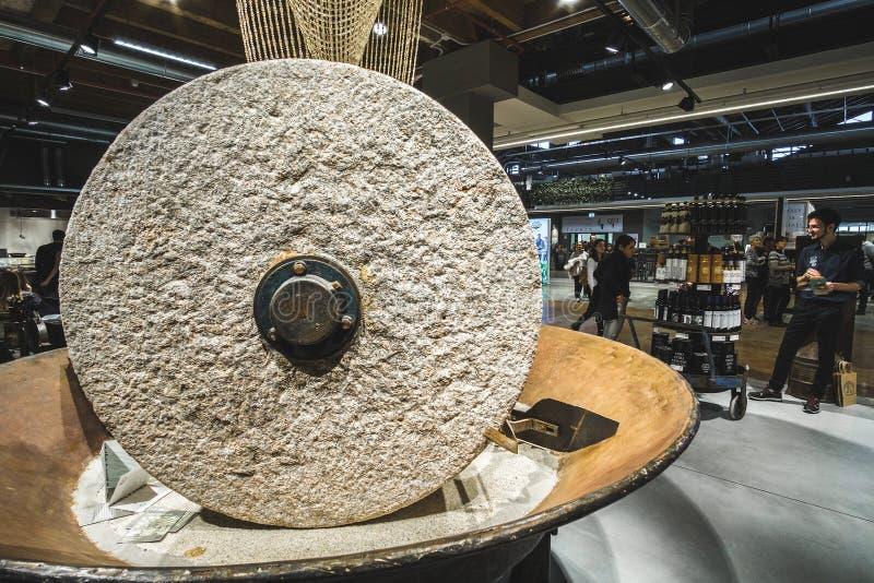 Las piedras de molino grandes muelen la rueda de piedra dentro del edificio moderno del mundo de Fico Eataly foto de archivo