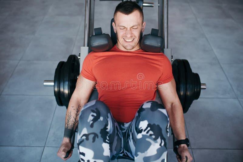 Las piernas aptas del entrenamiento del hombre en la pierna presionan la máquina en el gimnasio imagenes de archivo