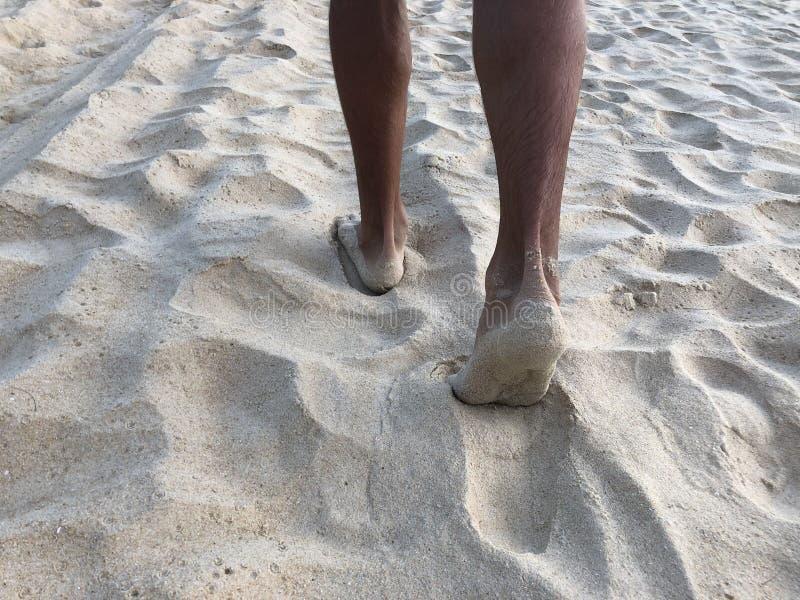 Las piernas bronceadas de los hombres en la arena fina blanca de la playa única de Karon de Phuket en el fondo del mar y de la pu fotografía de archivo