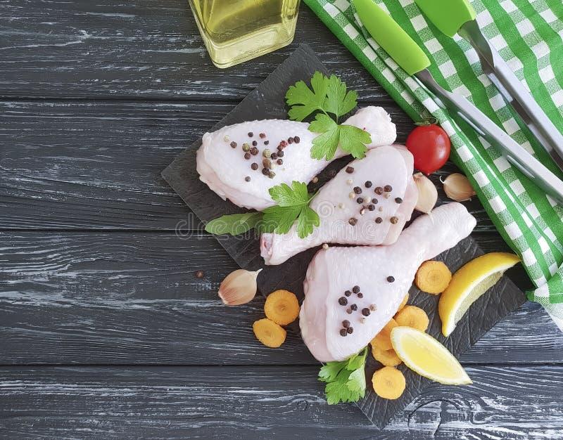 las piernas crudas del pájaro del pollo, limón, ajo, perejil, zanahorias, preparan el aceite en un fondo de madera negro fotografía de archivo