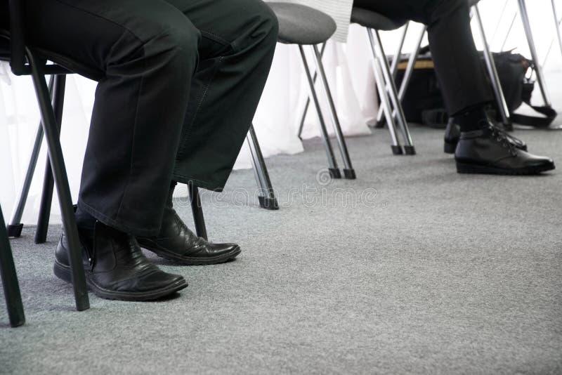 Las piernas de esperar de la gente su dan vuelta en sillas de la oficina en el vestíbulo Entrevista y búsqueda de trabajo imagen de archivo