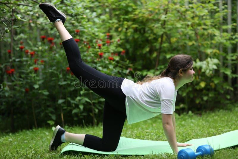 Las piernas de la elevación de la muchacha del adolescente hacen los ejercicios para el stomack plano con pesa de gimnasia imágenes de archivo libres de regalías