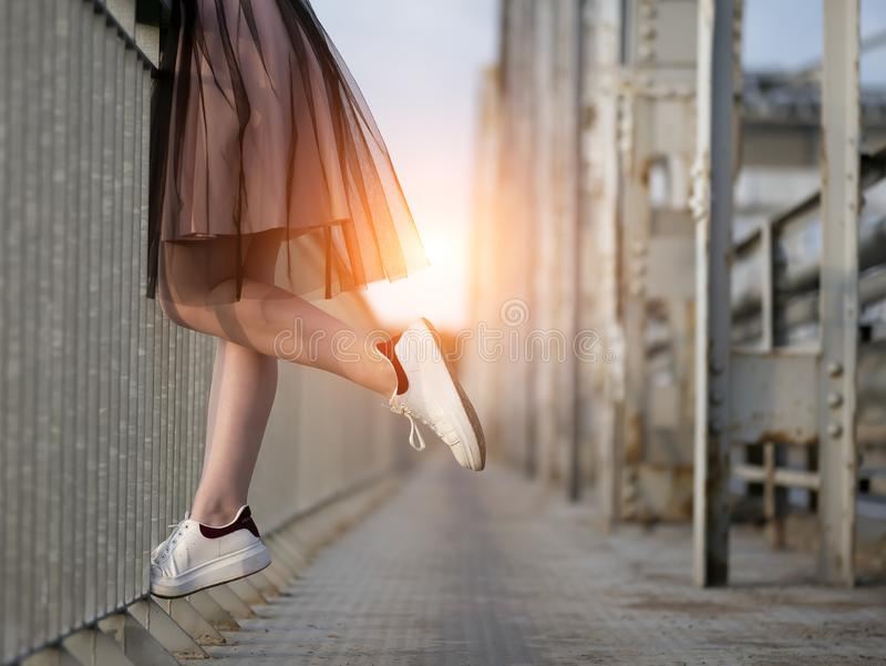 Las piernas de la muchacha adolescente en las zapatillas de deporte blancas en el puente en la puesta del sol imagenes de archivo