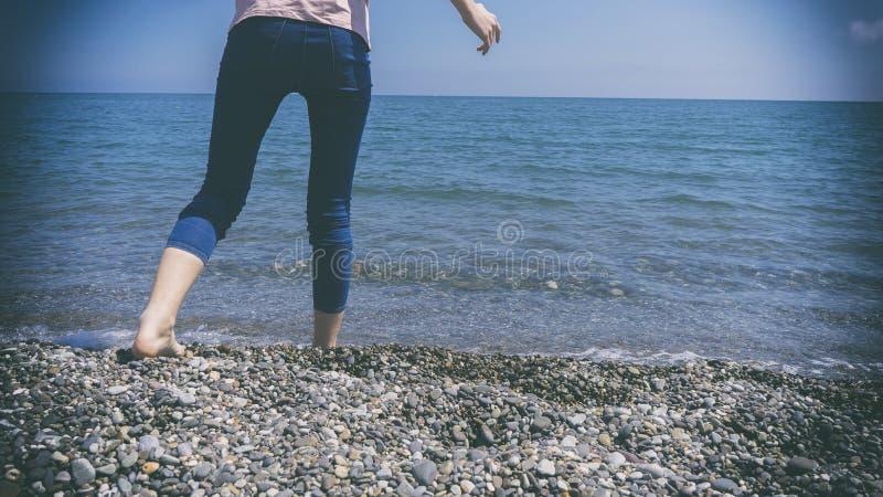 Las piernas de la mujer de jóvenes y bajar las piernas en un Pebble Beach por el mar azul hermoso imágenes de archivo libres de regalías