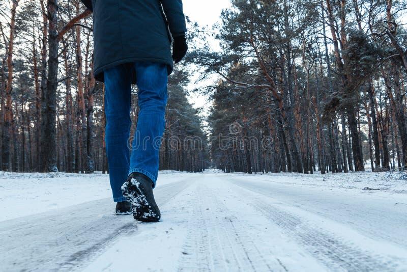 Las piernas de los hombres en las botas cercanas encima de la trayectoria nevada en el bosque del invierno imagenes de archivo
