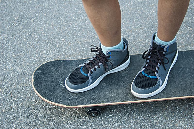 Las piernas de los niños en el skateboad en la calle imágenes de archivo libres de regalías