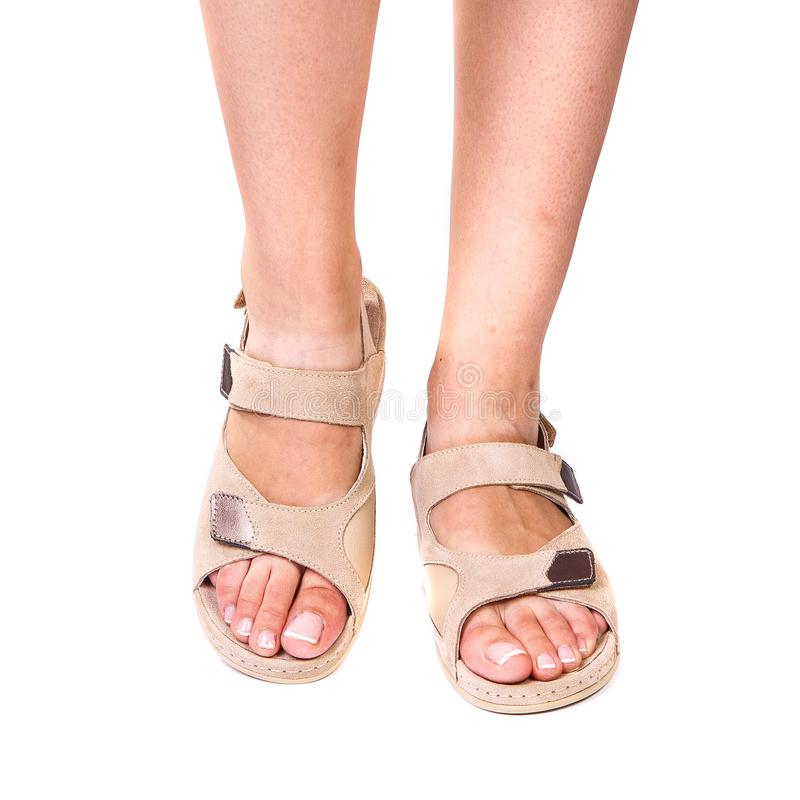 Las piernas de los zapatos ortopédicos de una muchacha en blanco aislaron el fondo fotos de archivo