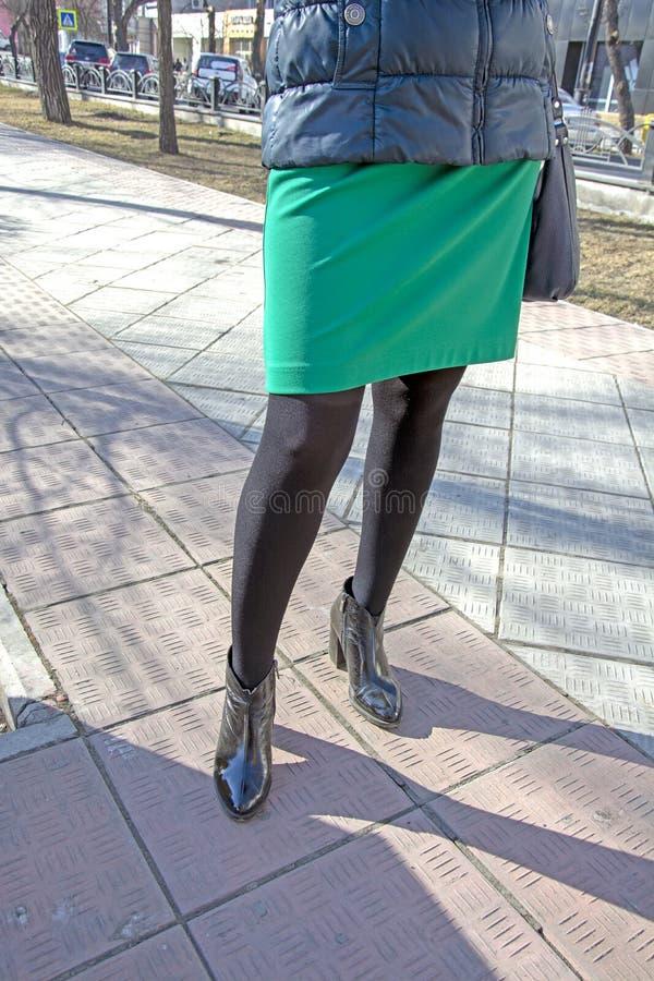 Las piernas de las mujeres en panty de nylon negro, en zapatos con los talones En la calle fetish foto de archivo