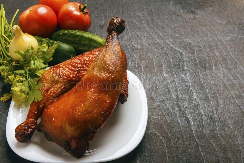 Las piernas de pollo cocinaron en una parrilla y verduras orgánicas frescas en un fondo negro Visión superior desde arriba Copie  fotos de archivo