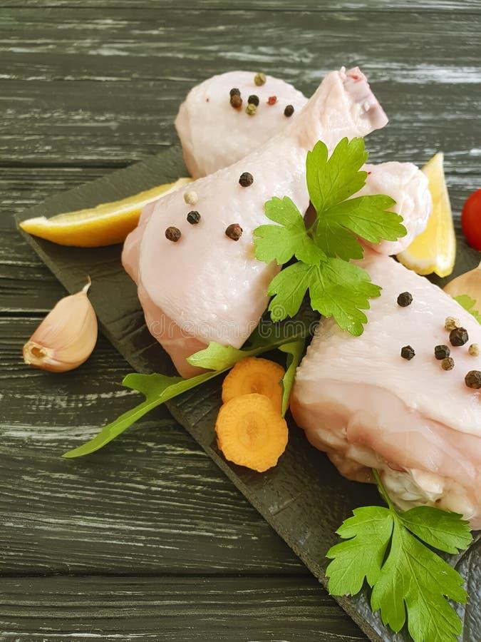Las piernas de pollo crudas, limón, ajo, ingrediente de la cena de la gastronomía del perejil de la cocina se preparan en un fond imagenes de archivo