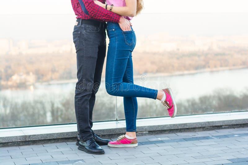 Las piernas de un individuo y de una muchacha que abrazan imagen de archivo