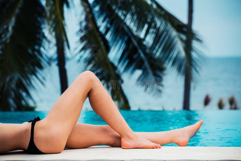 Las piernas de una mujer joven atractiva por una piscina fotografía de archivo libre de regalías
