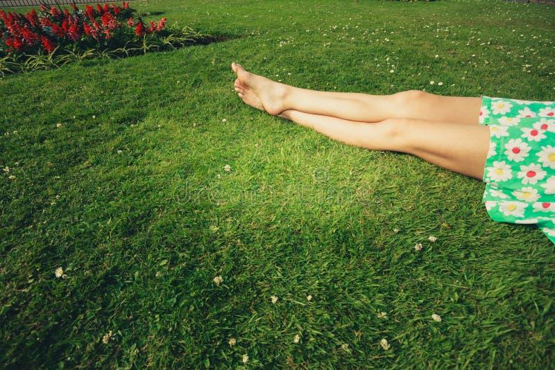 Las piernas de una mujer joven que miente en la hierba imagen de archivo libre de regalías