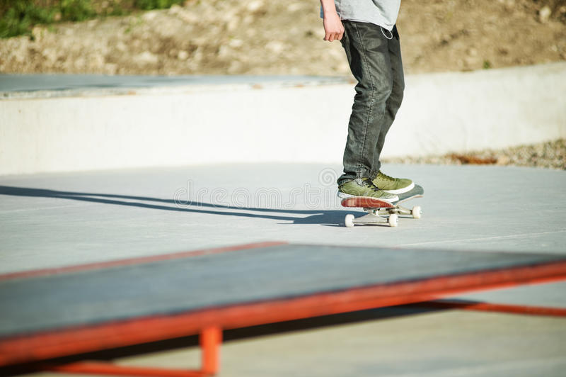 Las piernas del ` s del skater del primer andan en monopatín en el hormigón Patinaje en deportes populares del extremo de la juve fotografía de archivo libre de regalías