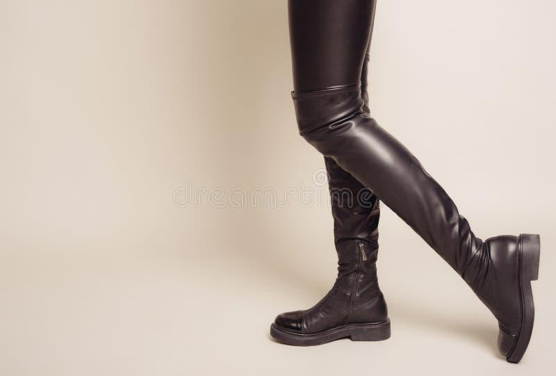 Las piernas delgadas del ` s de las mujeres en pantalones de cuero negros y altas botas elegantes se colocan de lado fotos de archivo