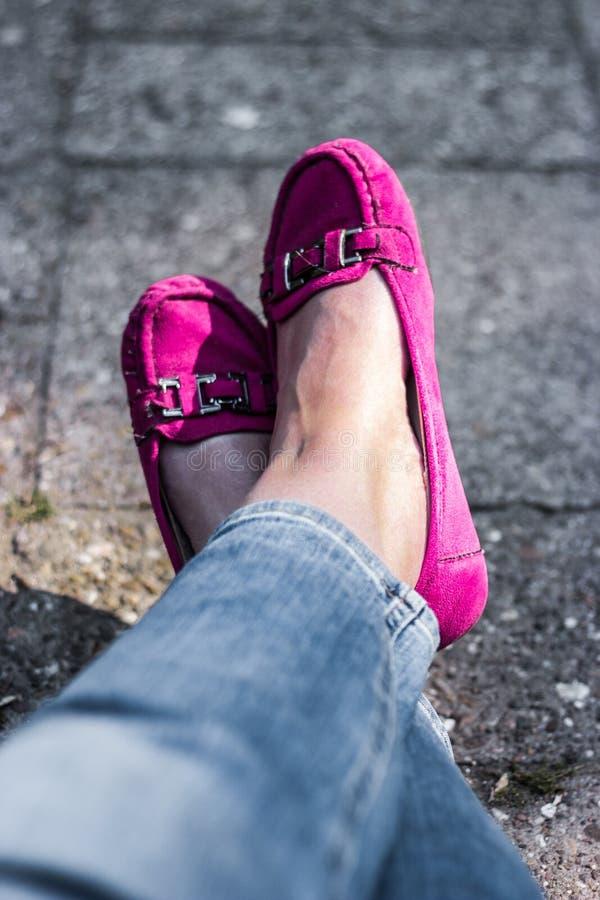 Las piernas en mocasines rosados, el sentarse de la mujer relajado fotos de archivo